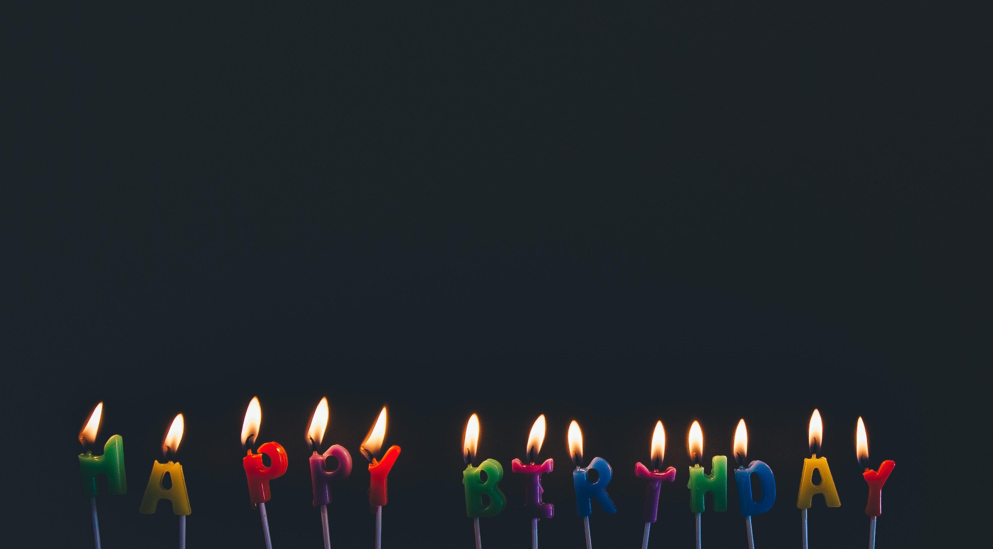 """Vor schwarzem Hintergrund stehen angezündete Kerzen, die gemeinsam """"Happy Birthday"""" ergeben."""